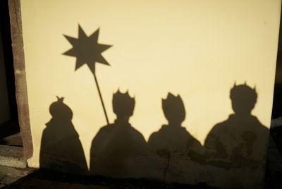 Der Schattenwurf einer Sternsingergruppe auf einer Hauswand. Der Schatten ist gestochen scharf und es sind sogar die Umhänge, Kronen und der Stern gut zu erkennen.