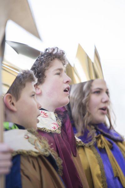 Drei Sternsinger gekleidet in Gewänder und mit Kronen auf dem Kopf singen eines des vielen Sternsingerlieder.