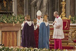 Drei Sternsinger stehen vor Papst Franziskus. Sie haben die traditionellen Gewänder an. Die Sternsinger haben an der Gabenprozession teilgenommen. Der Papst blick sie gütig und dankbar an. Er steht direkt vor ihnen und sitzt nicht auf seinem Goldenen mit rotem Samt bezogenen Stuhl.