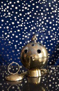 Ein Wichrauchgefäß steht vor einem dunkelblauem Hintergrund auf dem ganz viel helle Punkte wie Sterne funkeln.  Das Weihrauchgefäß ist geschlossen und raucht sanft.