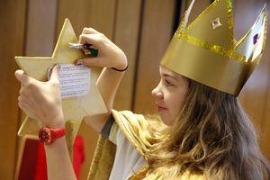 Alexandra klebt einen Liedzettel auf die Rückseite des Sterns. So kann sie den Text auch bei Aufregung nicht vergessen.