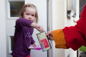 Ein kleines Mädchen spendet Geld und Schokolade an die Sternsinger.