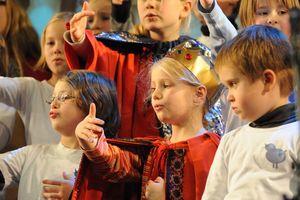 Eine größere Gruppe der Sternsinger singt zusammen ein Lied. Sie unterstreichen den Gesang durch ihre Gestik.