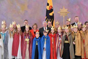 Neunzehn Sternsinger stehen in einer Gruppe zusammen mit Bundespräsident Joachim Gauck, seiner Lebensgefährtin und Prälat Krämer. Im Hintergrund ist die Nationalflagge von Deutschland zu sehen. Die Sternsinger tragen Umhänge in Rot, Blau und Grün. Alle Sternsinger tragen goldene Kronen. Im Hintergrund hält einer der Sternsinger den Stern von Betlehem in die Luft.
