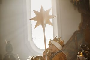 Der Stern der Sternsinger wird durch das Licht das durch ein Kirchenfenster fällt erleuchtet.