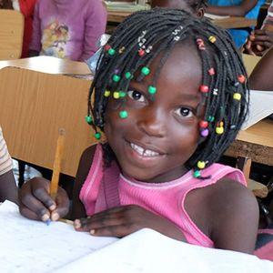 Ines sitzt mit einem Klassenkameraden in der Klasse am Tisch. Beide haben Hefte aufgeschlagen und Stifte in der Hand und sind froh darüber lernen zu dürfen.
