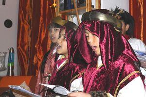 Eine Sternsingergruppe hält Textblätter in der Hand und singt. Sie trän Kronen und die traditionelle Kleidung der Heiligen Drei Könige.