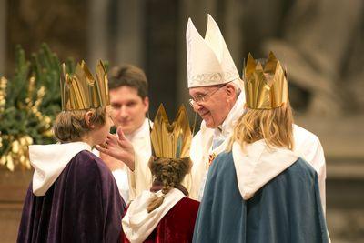 Drei Sternsinger stehen vor Papst Franziskus. Sie haben die traditionellen Gewänder an. Die Sternsinger haben an der Gabenprozession teilgenommen. Der Papst steht direkt vor den Sternsinger und blickt Ihnen und ie Augen. Er berührt einen der Sternsinger sanft mit der Hand an der Wange.
