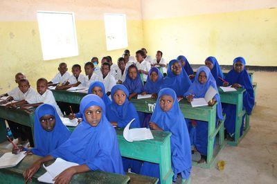 Auf dem Bild ist eine Schulklasse in Somalia zu sehen: Die Jungen tragen weiße Hemden, die Mädchen tragen blaue Hidschabs.