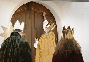 Drei Sternsinger schreiben den traditionellen Segen der Sternsinger an eine Haustür. Die Sternsinger tragen Kronen, den Stern und die traditionellen Gewänder der Heiligen Drei Könige.