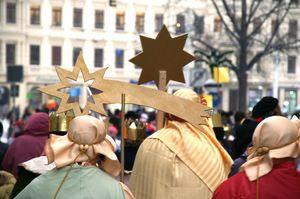 Vier Sternsinger gehen in einem Wohngebiet von Haus zu Haus. Sie tragen den Stern, Kronen und leuchtende bunte Gewänder und Umhänge.