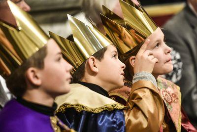 Drei Sternsinger sitzen nach der Gabenprozession im Petersdom und verfolgen den Gottesdienst mit dem Papst. Die Sternsinger haben die Gewänder und Kronen an. Einer der Sternsinger hat den Arm leicht erhoben und deutet mit dem Zeigefinger auf etwas. Einer der anderen Sternsinger folgt mit seinem Blick.