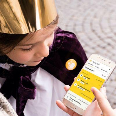 Sternsinger schauen zusammen auf die mobile Sternsinger-App