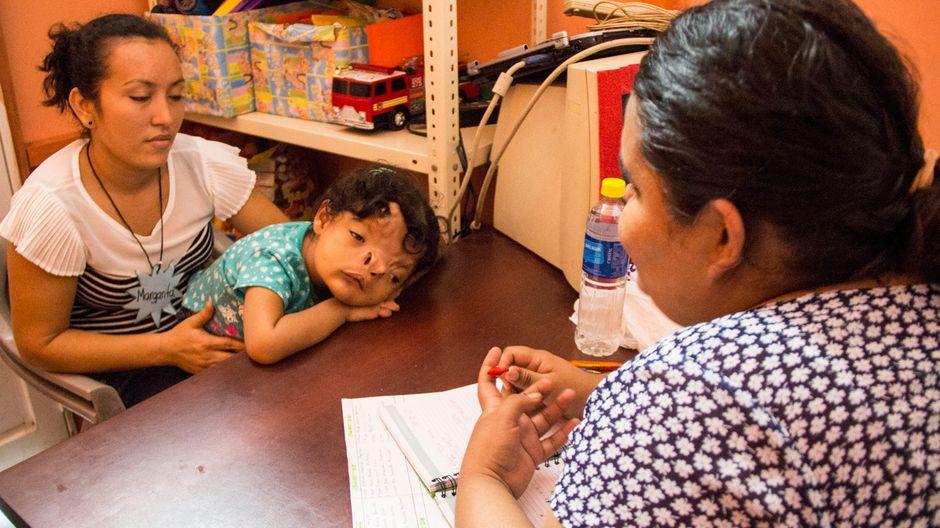 Eine Frau besucht mit ihrem schwerbehinderten Kind die Beratungsstelle der Einrichtung.