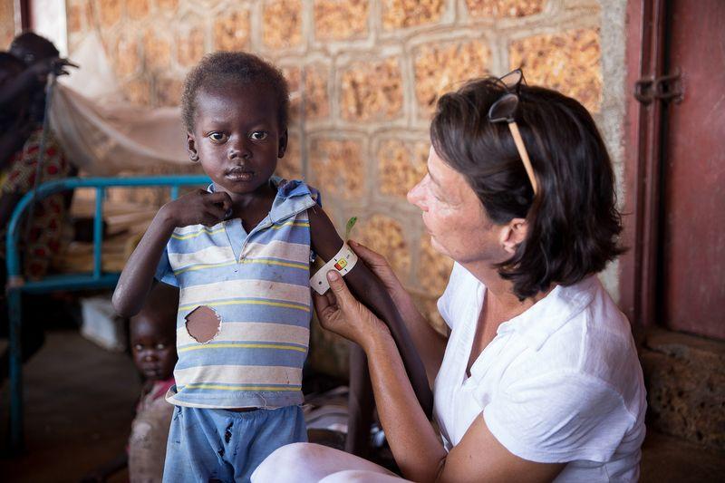 Krankenschwester Tatjana Gerber (AGEH) misst den Armumfang von Dut (3). Er hat keine Mutter mehr und seine Schwester Ajuen (10) kuemmert sich um. Dut ist traumatisiert und unterernaehrt. Sie nehmen teil am Ernaehrungsprogramm auf dem Gelaende des Mary Help Krankenhaus in Sokolona/Wau (c) Kathrin Harms/Sternsinger
