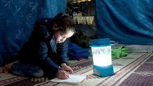 Weil es draußen zu gefährlich zum Spielen ist, verbringen Nour und ihre Geschwister viel Zeit im Zelt. Am liebsten sitzt Nour wie hier auf dem Boden und malt Bilder.
