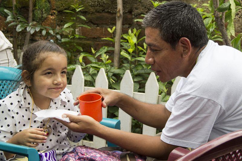 Ein Vater füttert liebevoll seine Tochter.