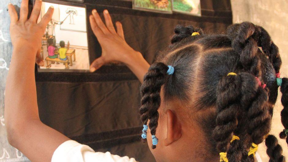 Ein Mädchen lernt anhand von bunten Karten mit Tieren.