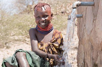 Aweet an einem Brunnen mit frischem Wasser. Sie lächelt und ist glücklich über die Wasserquelle.