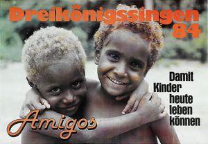"""Ein Plakat zu Bewerbung der Aktion Dreikönigssingen 1984. Abgebildet sind zwei Kinder die sin gegenseitig in den Armen halten und freudig lachen. Beide Kinder haben kurze stark gelockte Haare und tragen keine Kleidung am Oberkörper. Unten links in der Ecke des Plakates steht das Wort """"Amigos"""" Das bedeutet Freunde. In der rechten Ecke steht der Slogan """"Damit Kinder heute leben können."""" Am Kopfende des Plakats steht in orange farbebner Schrift Dreikönigssingen´84."""