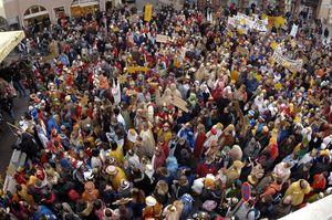 Der Platz vor der großen Bühne in Speyer ist brechend voll mit Sternsingern. Alle haben bunte Umhänge und glänzende Kronen na. Es ist wildes Farbenmeer. Es sind sogar zwei Menschen sehen die sich als Kamel verkleidet haben. Viele Sternsinger blicken herauf zur Kamera und winken. Auf den zahlreichen Sternen und Bannern steht drauf woher die Sternsinger kommen und welche Forderungen sie vertreten wollen.