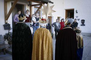 Eine Familie hört aufmerksam den Sternsinger beim Singen zu. Die Sternsinger haben Umhänge und Kronen an und tragen den Stern vor sich.