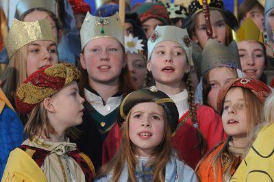 Eine große Gruppe der Sternsinger singt ein Lied. Alle haben die Gewänder und Kronen an. Manche Kronen sind reich geschmückt.