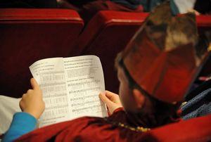 Ein Sternsinger sitzt in einer Kirchenbank und liest sich den Text zur Segnung der Kreide durch.