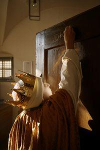 Ein Sternsinger mit Krone und gekleidet in ein Gewand, schreibt den traditionellen Segen der Sternsinger an eine Haustür. Der Sternsinger muss sich Strecken um bis ganz nach oben zu kommen.