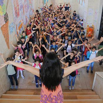 Schülerinnen und Schüler der Schule in Latakia strecken die Arme in die Luft.