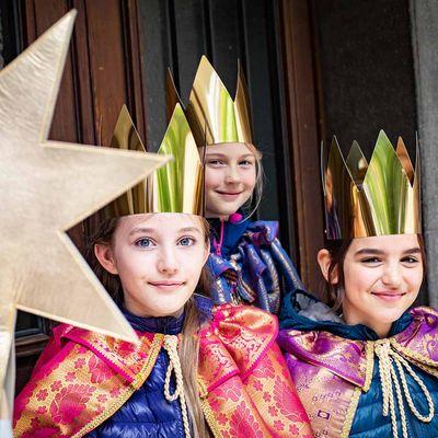 Drei Sternsingerinnen lächeln in die Kamera.