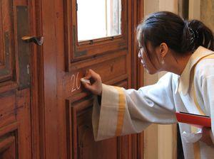 Eine Sternsingerin gekleidet in ein traditionelles Gewand der Heiligen Drei Könige schreibt mit Kreide den Segen der Sternsinger an eine Haustür.