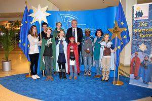 Die Sternsinger zu Gast im EU- Parlament. Vizepräsident des EU- Parlaments, Rainer Wieland, empfängt und begrüßt sie. Die Sternsinger aus der Pfarrei St. Rochus aus dem Seelsorgebereich Kerpen Süd- West haben bunte Umhänge und goldene Kronen an. Rainer Wieland steht in der Mitte des Sternsingergruppe.