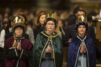Drei Sternsinger beim Gebet im Petersdom. Sie haben an der Gabenprozession mitgewirkt und tragen die Sternsingergewänder. Zusätzlich haben sie goldene Kronen auf dem Kopf. die Die Sternsinger haben andächtig die Hände vor der Brust gefaltet.