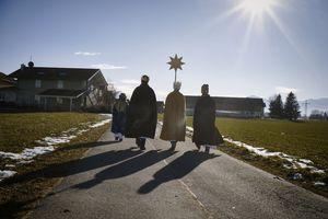Drei Sternsinger tragen den Stern voran und befinden sich auf dem Weg zu einem Haus. Die Sonne scheint.
