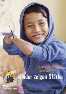 Das Plakat zur Aktion Dreikönigssingen 2011.  Abgebildet ist ein Junge in einem blauen Kapuzenpullover. Der Junge lächelt und hat die Ärmel des Pullovers bis der die Ellbogen hoch gekrempelt. Der junge hat keine Hände mehr. Seine Arme hören auf halbem Weg zwischen Ellbogen und Handgelenk auf. Mit den Enden seiner Arme hält der Junge einen Pinsel fest um mit diesem Pinsel zu malen. In der Fußzeile des Plakats steht Kinder zeigen Stärke. Auf Khmer kmäng kmäng bong- nein kam- lahng. Auch das bedeutet Kinder zeigen Stärke. Unten links in der Ecke das Plakats ist das Logo der Sternsinger und der Schriftzug Aktion Dreikönigssingen.