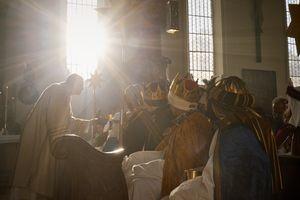 Sternsinger wohnen einem Gottesdienst bei. Die Sternsinger sitzen und er ersten Reihe und der Priester geht herum und segnet die Sternsinger. Die Kinder haben aufwändige Kostüme und Kronen an.
