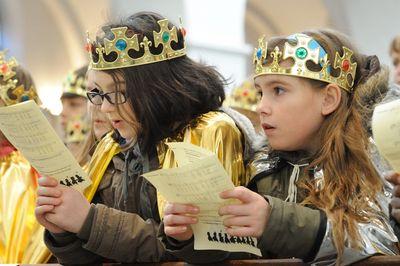 Sternsinger bei einer Zeremonie in einer Kirche. Sie haben Kronen und Gewänder an und halten Lidtexte vor sich. Die Sternsinger singen mit.
