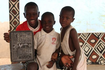 Ein älterer Jugendlicher und zwei junge Kinder die wieder zur Schule gehen können präsentieren stolz wie gut sie schon lesen und schreiben können.