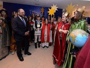 Martin Schulz hört den Sternsingern aufmerksam zu. Die erklären ihm nämlich grade sein Geschenk. Sein Geschenk ist ein Globus und die Sternsinger zeigen ihm auf dem Globus wo überall auf der Welt die Sternsinger helfen. Martin Schulz versprach den Globus an einem Ehrenplatz aufzustellen.