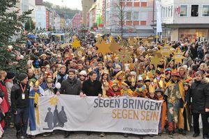 n einem farbenfrohen Festzug zogen die Sternsinger zum Würzburger Kiliansdom. Die Straße die normalerweise voll Autos ist, ist jetzt gefüllt mit Sternsingern.