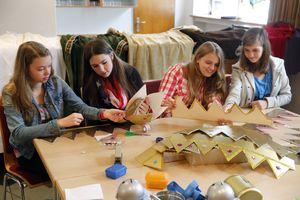 Die Sternsinger Alexandra, Jana, Alina und Carolin sitzen an einem großen Tisch uns basteln Kronen. Sie bereiten sich auf die Sternsingeraktion vor und verzieren die Kronen mit vielen Detailwie glitzerndem Staub und funkelnden Steinen.