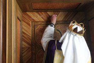 Ein Sternsinger mit Krone und Gewand schreibt den traditionellen Segen der Sternsinger, mit Kreide, an eine Haustür.