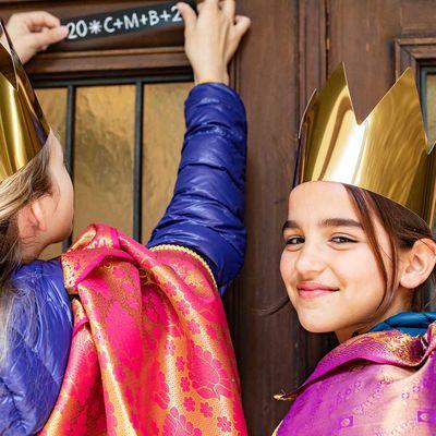Zwei Sternsingerinnen kleben an einer Haustür den Segen an.