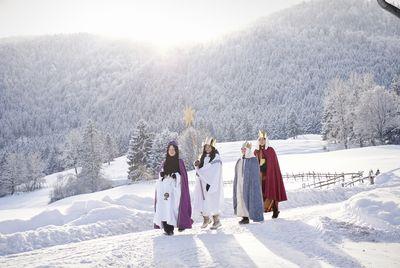 Vier Sternsinger gehen im Gänsemarsch durch eine tief eingeschneite Landschaft. Sie trotzen Schnee und Eis um den Segen zu den Menschen zu tragen und Spenden für bedürftige zu sammeln.