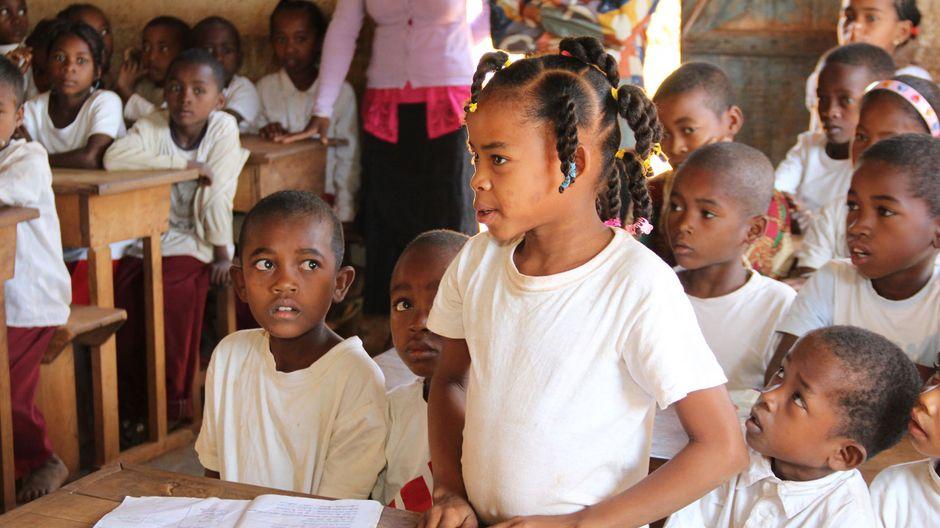 Ein junges Mädchen steht in der Klasse und beantwortet eine Frage.