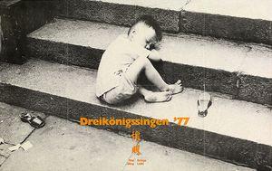 Ein Plakat der Sternsinger von 1977. Das Motiv ist ein schwarz- weiß Fotos eines kleinen Junge der zusammengekauert auf Treppenstufen schläft. Er trägt ein Hemd und eine kurze Hose, trägt jedoch keine Schuhe an den Füßen. Auf der Treppe auf der er schläft liegt Müll herum. Mittig in der Fußzeile des Plakats steht in oranger Farbe Dreikönigssingen´77 gefolgt von zwei chinesischen Schriftzeichen. Diese Zeihen bedeuten Wei Ming. Das heißt Bringe Licht.