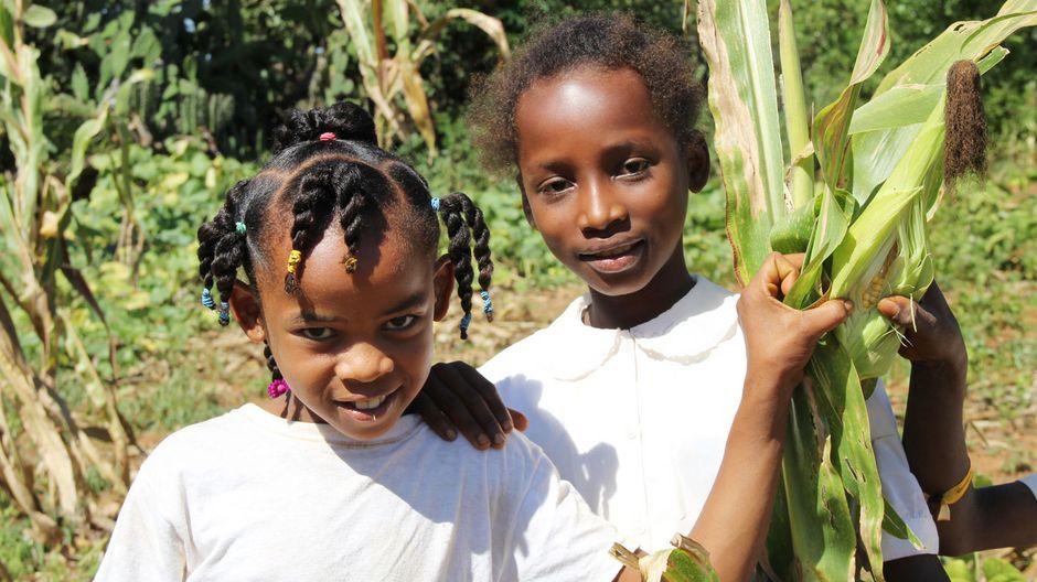 Zwei Mädchen stehen glücklich im Grünen.