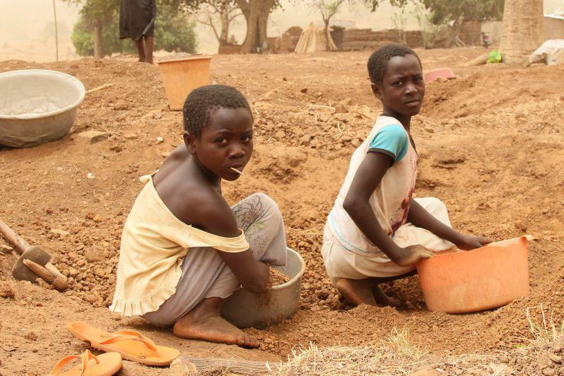 Zwei Jungs die in einer Mine arbeiten. Sie sieben den staubigen Boden auf der suche nach Gold.