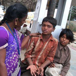 Eine Streetworkerin spricht mit Straßenkindern und kümmert sich um sie.